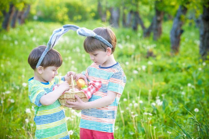 Ungar på jakt för påskägg i blommande vår arbeta i trädgården Barn bryner arkivfoton