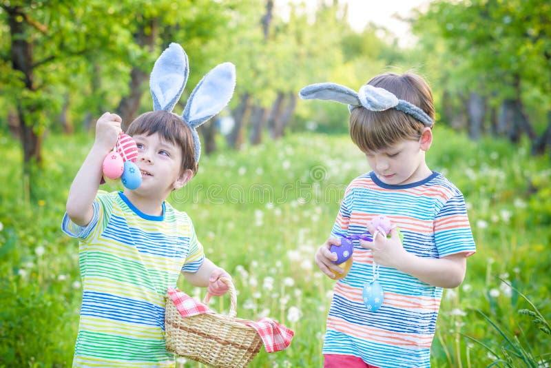 Ungar på jakt för påskägg i blommande vår arbeta i trädgården Barn bryner fotografering för bildbyråer