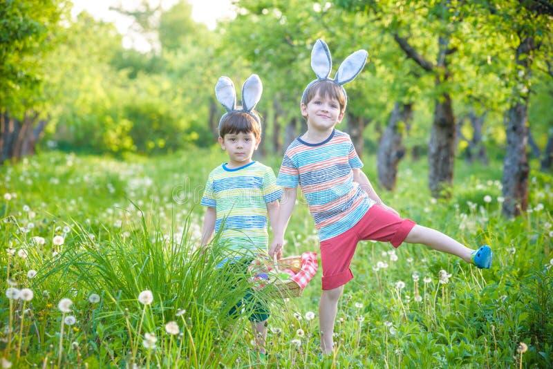 Ungar på jakt för påskägg i blommande vår arbeta i trädgården Barn som söker för färgrika ägg i blommaäng Litet barnpojke och han royaltyfria bilder
