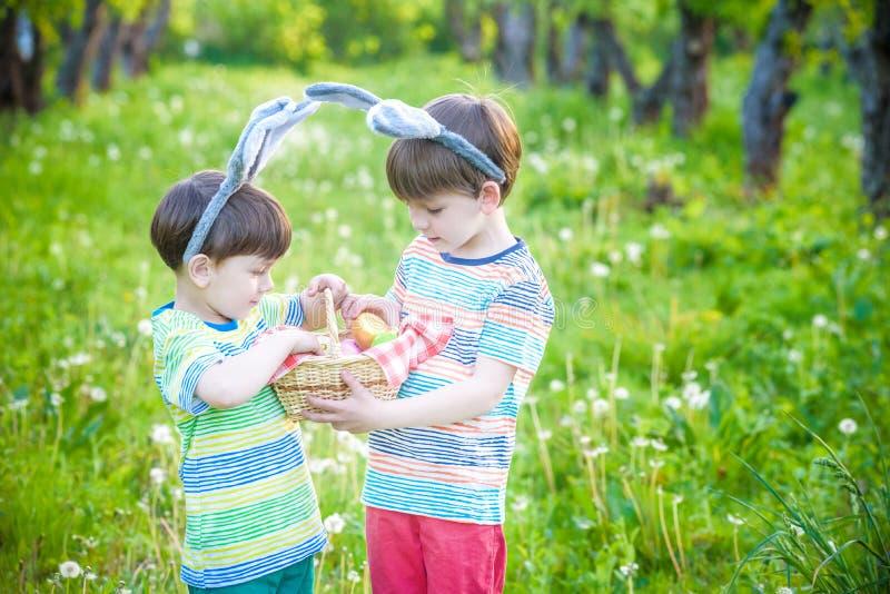 Ungar på jakt för påskägg i blommande vår arbeta i trädgården Barn som söker för färgrika ägg i blommaäng Litet barnpojke och han arkivfoto