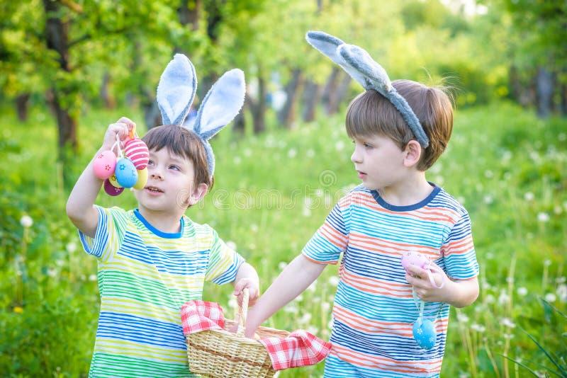 Ungar på jakt för påskägg i blommande vår arbeta i trädgården Barn som söker för färgrika ägg i blommaäng Litet barnpojke och han arkivfoton