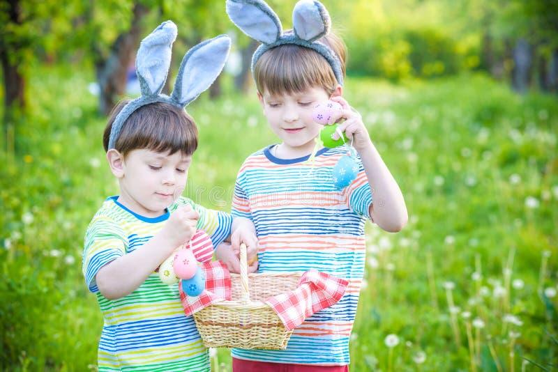 Ungar på jakt för påskägg i blommande vår arbeta i trädgården Barn som söker för färgrika ägg i blommaäng Litet barnpojke och han arkivbilder