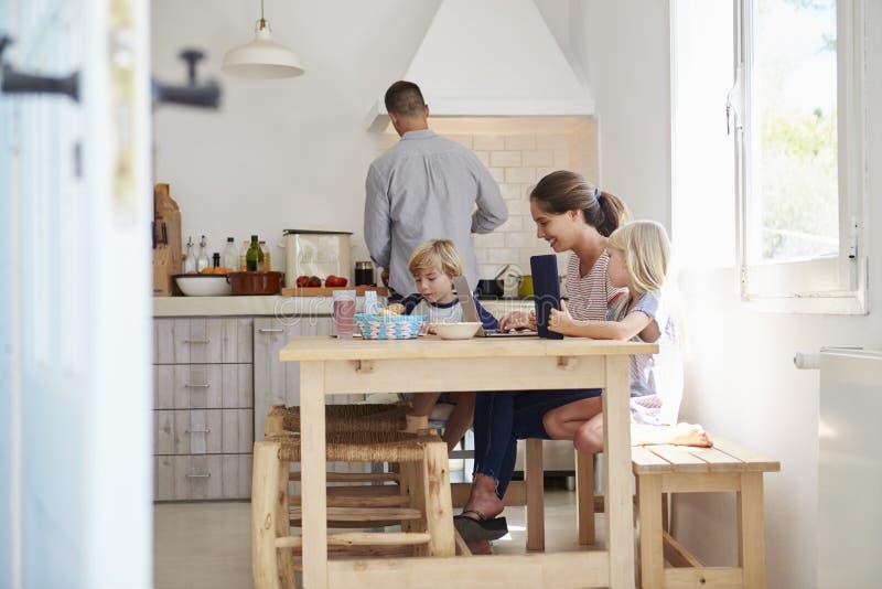 Ungar på köksbordet med mumen, farsakockar, sikt från dörröppningen royaltyfria bilder