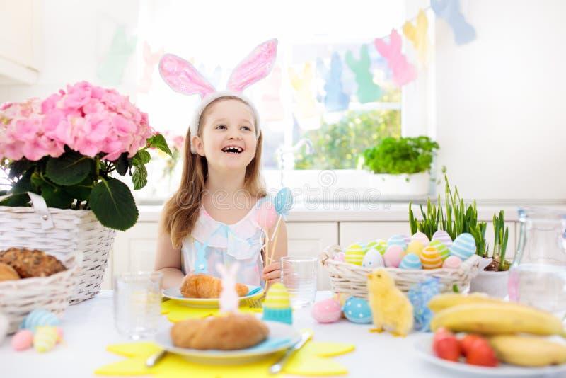 Ungar på påsken frukosterar äggkorgen, kaninöron royaltyfri fotografi