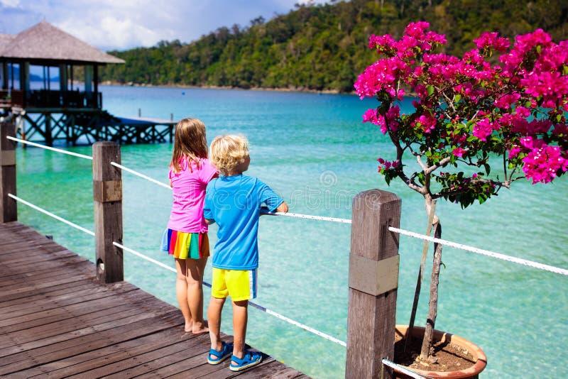Ungar p? den tropiska stranden Barn på semesterortbryggan arkivfoto