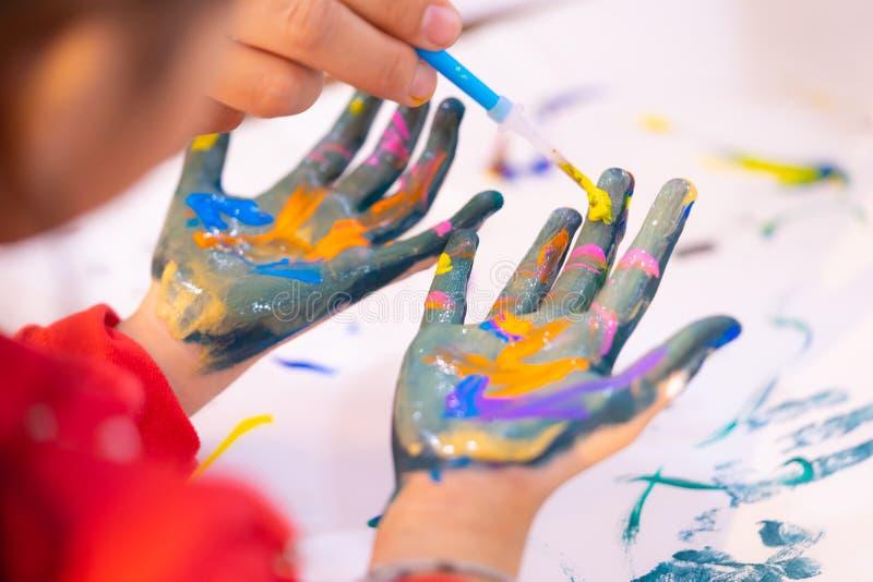 Ungar smutsar ner den målade handen i konstklassrum royaltyfri fotografi