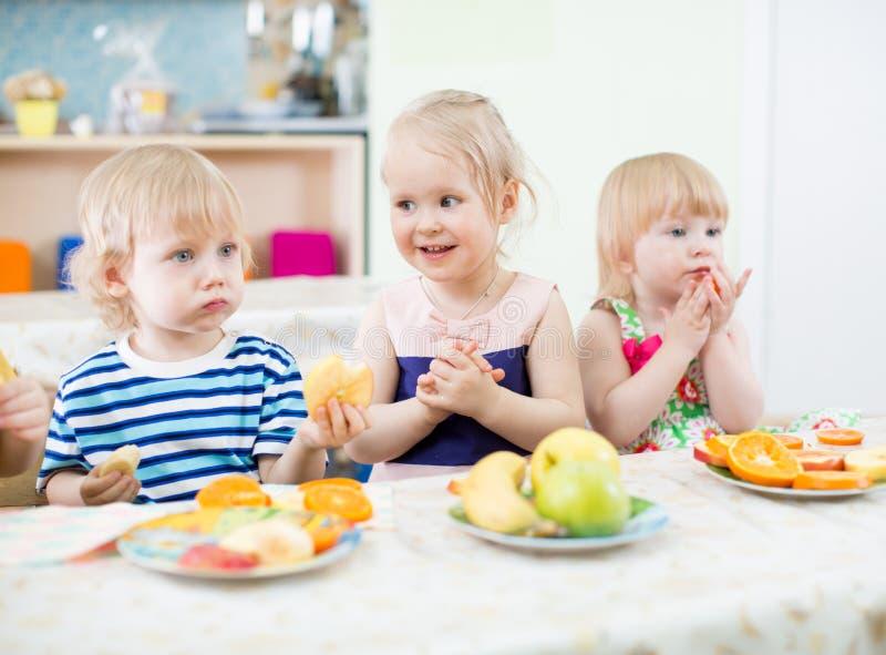Ungar som äter frukter i dinning rum för dagis arkivfoton