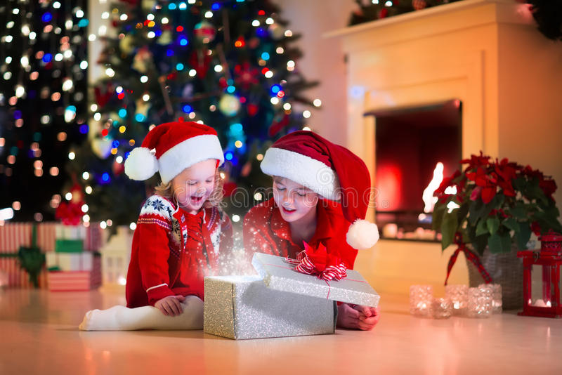 Ungar som öppnar julklappar arkivfoto