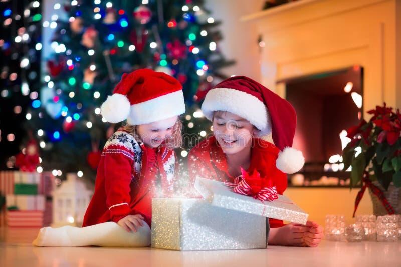 Ungar som öppnar julklappar arkivfoton