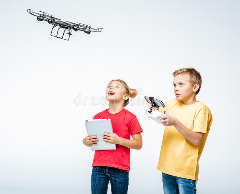 Ungar som använder den digitala minnestavlan och hexacoptersurret royaltyfri fotografi