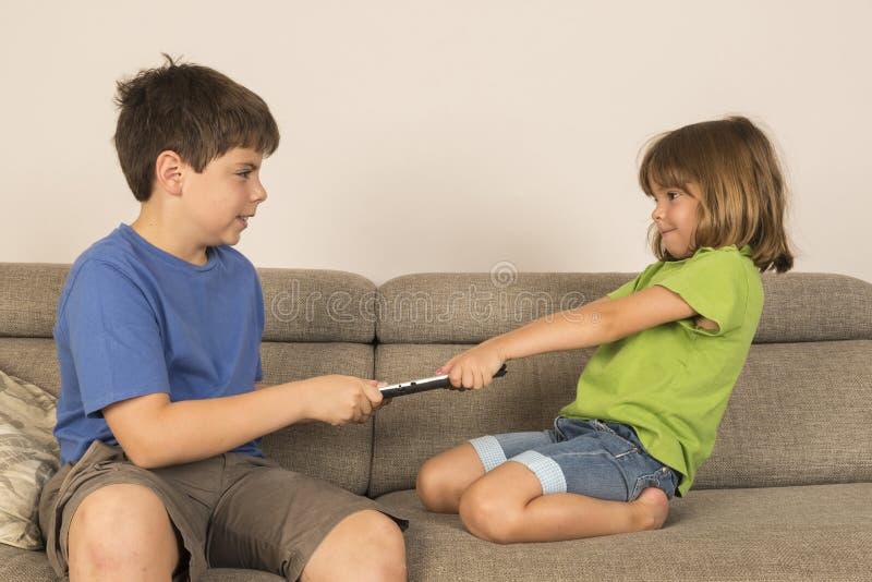 Ungar som argumenterar för att spela med en digital minnestavla arkivfoto