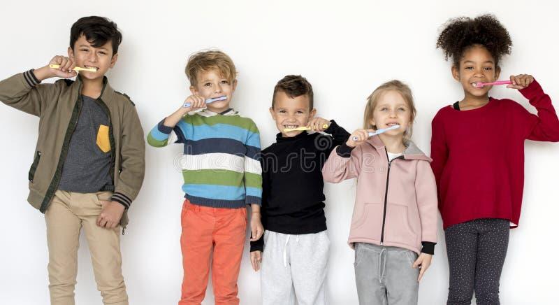 Ungar som borstar deras tänder som isoleras på vit bakgrund royaltyfri fotografi