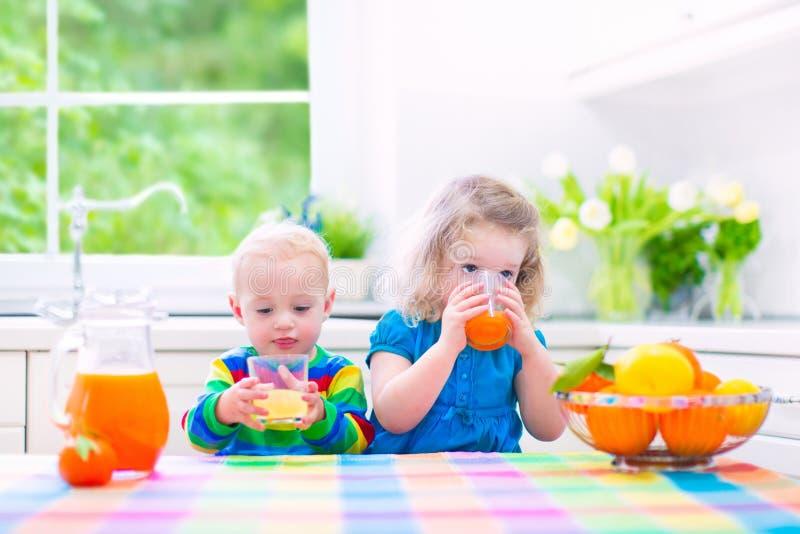 Ungar som dricker orange fruktsaft arkivbild