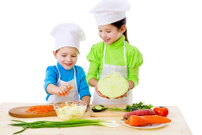 ungar som förbereder sallad som ler två arkivbild
