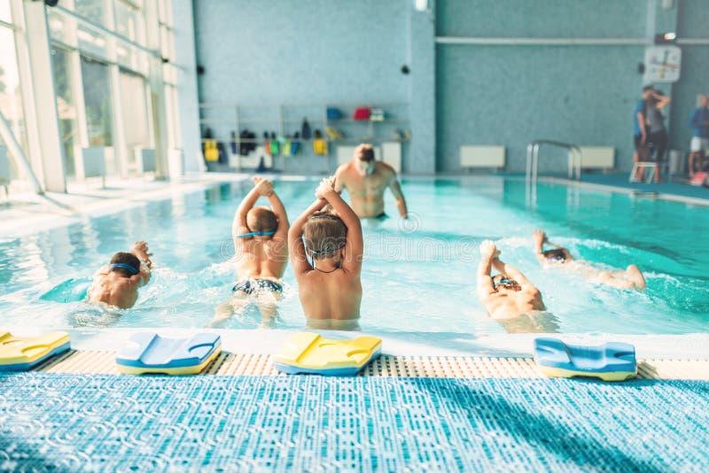 Ungar som försöker att dyka i simbassäng arkivfoto