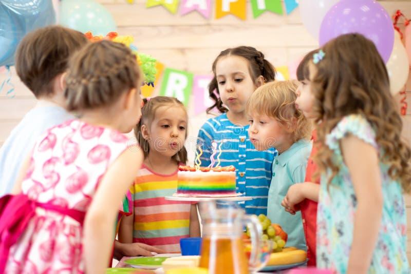 Ungar som firar f?delsedagpartiet och bl?ser stearinljus p? kakan royaltyfri foto