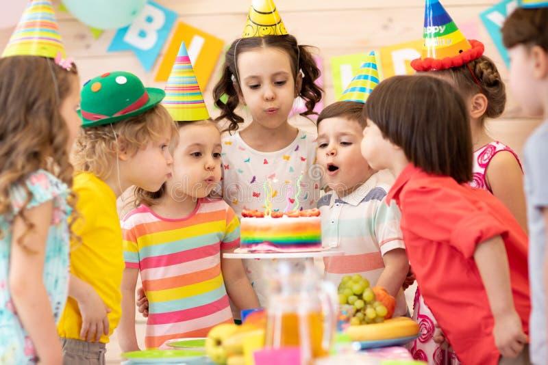 Ungar som firar f?delsedagpartiet och bl?ser stearinljus p? kakan fotografering för bildbyråer