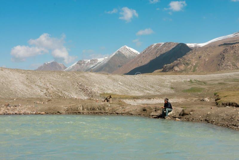 Ungar som fiskar i en blå bergflod på den soliga morgonen med snö, vaggar royaltyfri foto