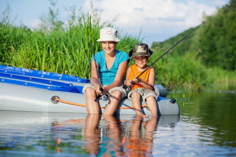 Ungar som fiskar på floden royaltyfri fotografi