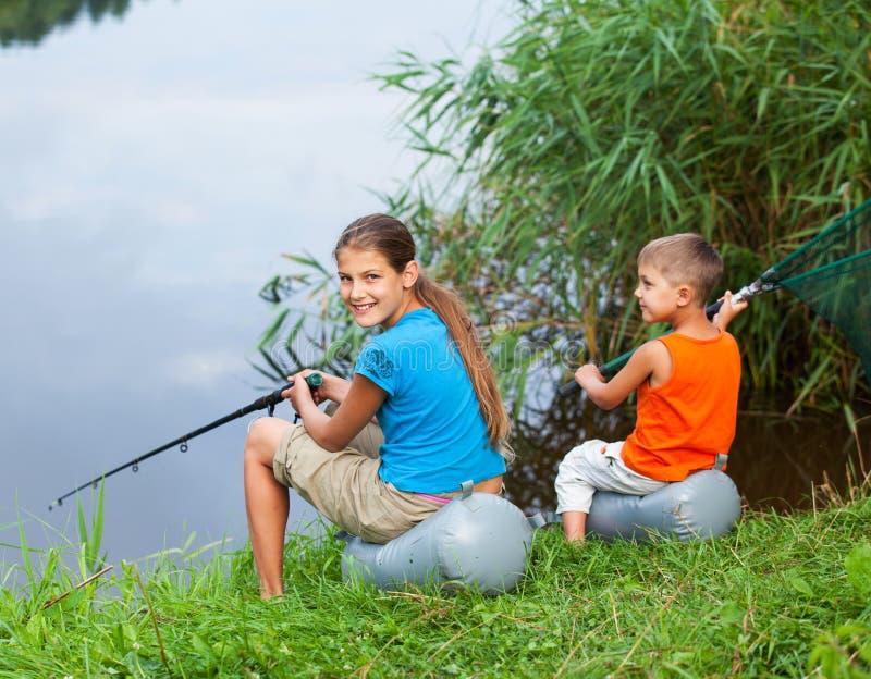 Ungar som fiskar på floden fotografering för bildbyråer