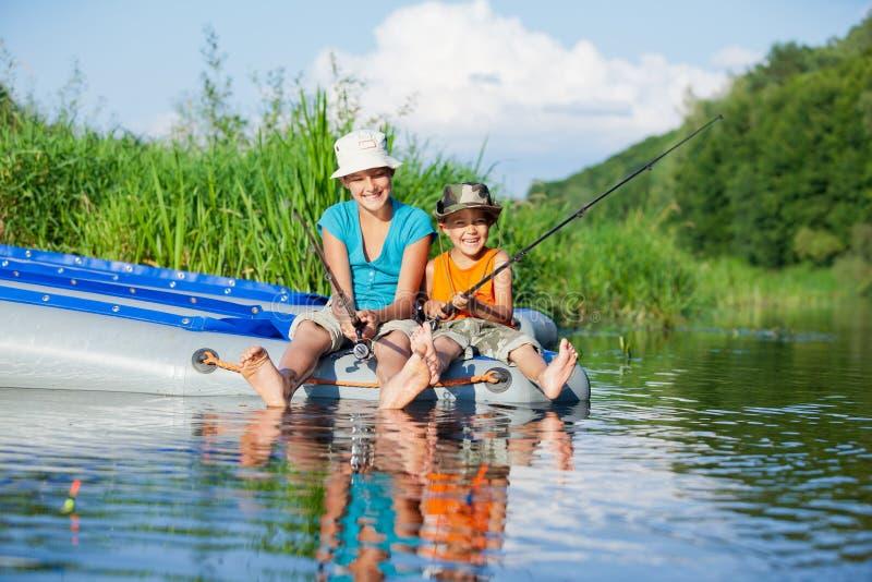 Ungar som fiskar på floden arkivfoto