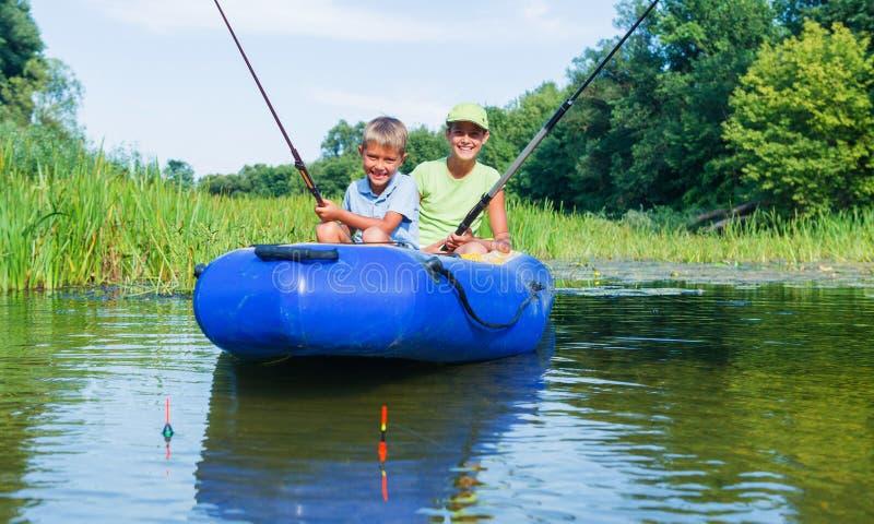Ungar som fiskar på floden arkivfoton