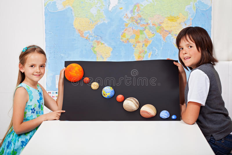 Ungar som framlägger deras vetenskapshemprojekt - solsystemet arkivbilder