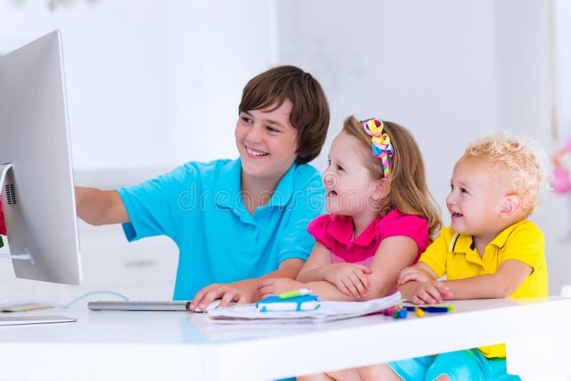 Ungar som gör läxa med den moderna datoren royaltyfri foto