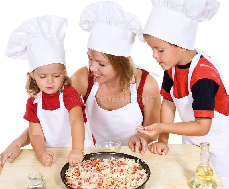 ungar som gör pizza royaltyfria foton