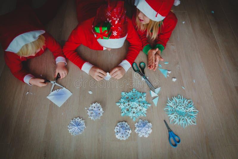 Ungar som gör snöflingor från papper, julhantverk arkivfoto