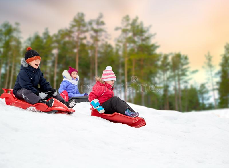 Ungar som glider på slädar snöar ner, kullen i vinter arkivbilder
