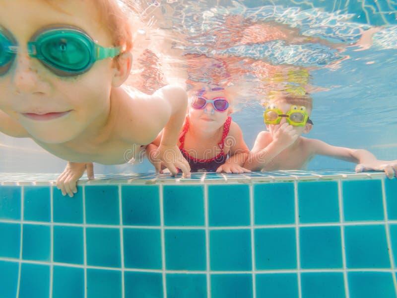 Ungar som har att spela f?r gyckel som ?r undervattens- i simbass?ng p? sommarsemester royaltyfria bilder