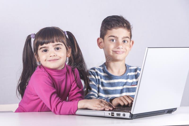 Ungar som har gyckel genom att använda en bärbar datordator royaltyfria foton
