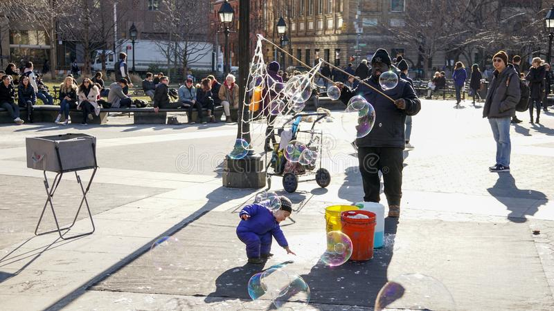 Ungar som har gyckel med slaget, bubblar i Manhattan, New York City royaltyfria bilder