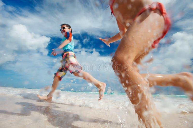 Ungar som har gyckel på stranden