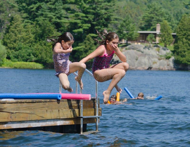 Ungar som har roligt hoppa för sommar av skeppsdocka in i sjön arkivfoto
