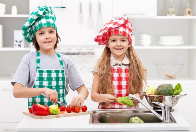 Ungar som hjälper i köket - tvagning och skivar grönsaker arkivbilder