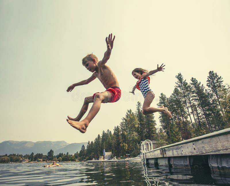 Ungar som hoppar av skeppsdockan in i en härlig bergsjö royaltyfri bild