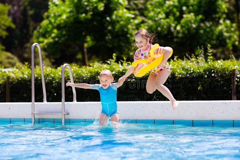 Ungar som hoppar in i simbassäng royaltyfri foto