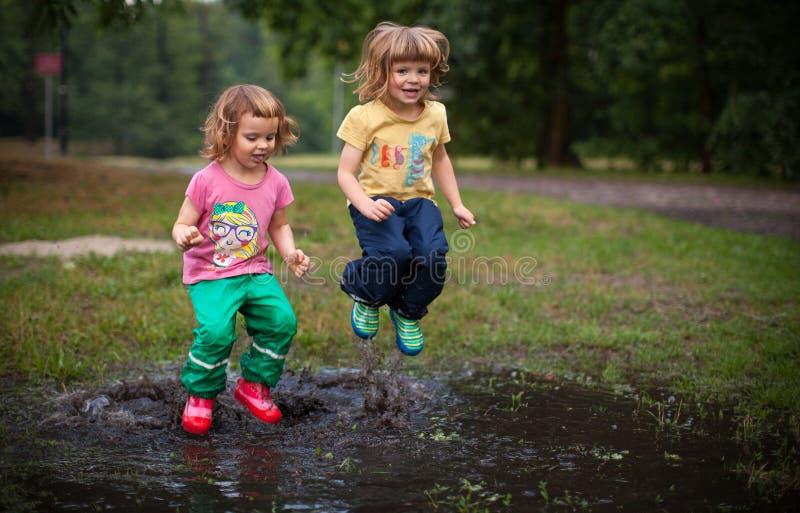 Ungar som hoppar in i vattenpöl royaltyfri foto