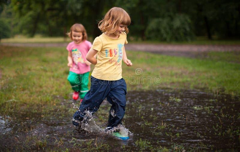Ungar som hoppar in i vattenpöl royaltyfria bilder