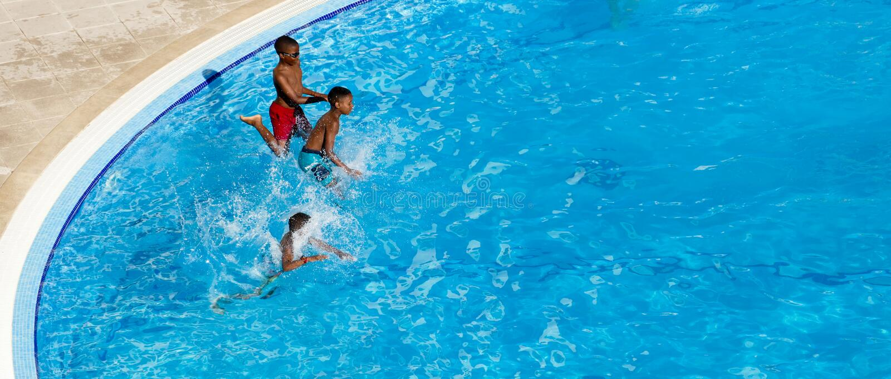 Ungar som in hoppar till simbassängkonkurrens arkivbilder