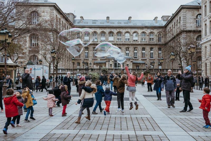 Ungar som jagar jätte- såpbubblor på en gata i Paris, Frankrike royaltyfri bild