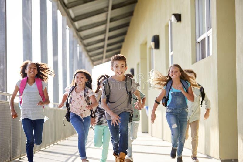 Ungar som kör i grundskolakorridoren, slut upp arkivfoton