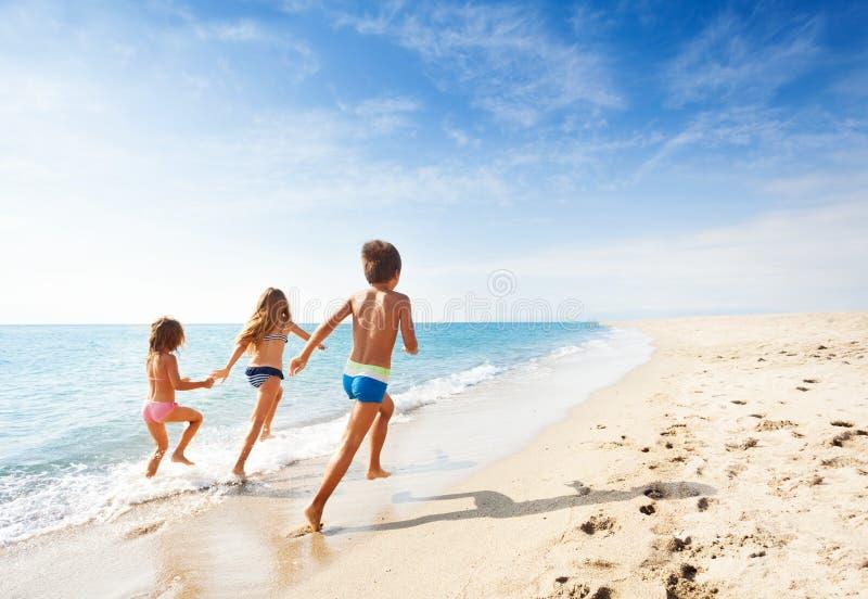 Ungar som kör längs stranden under sommarsemester arkivbild