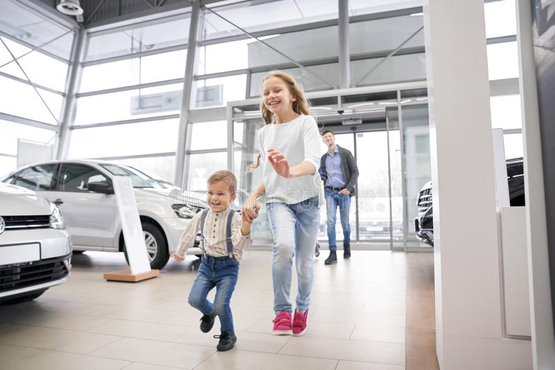 Ungar som kör och skrattar i salong med bilar royaltyfria foton