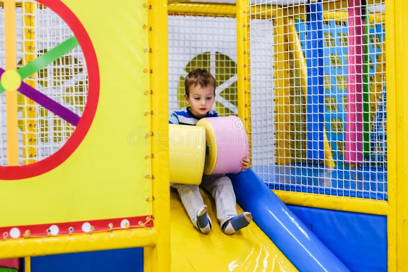 Ungar som klättrar och glider på utomhus- lekplats Barnlek i inomhus lekplats Munterhetmitt i dagis- eller skolaya arkivbilder
