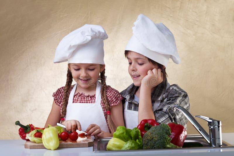 Ungar som klipper grönsaker för en sallad royaltyfri foto