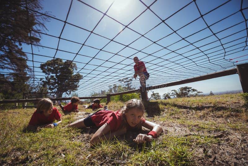 Ungar som kryper under det netto under utbildning för hinderkurs royaltyfri foto