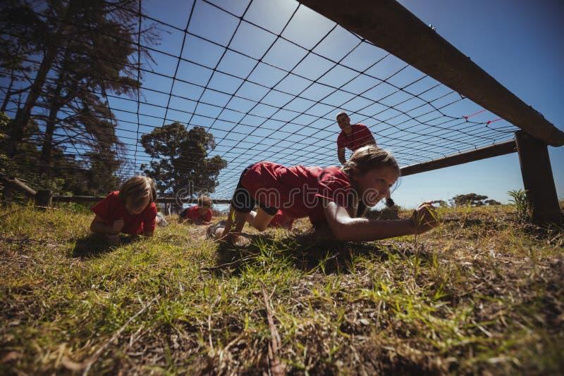 Ungar som kryper under det netto under utbildning för hinderkurs arkivfoto